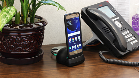 Samsung phone in intelliskin on desk top charger in office